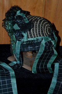 Woven ribbon curtain and ties over a straw bonnet.